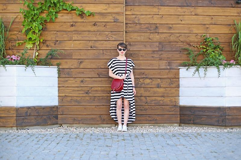 Stylizacja z pasiastą sukienką, czerwoną torebką i białymi trampkami