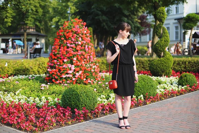 Uniwersalna czarna sukienka i czerwona torebka