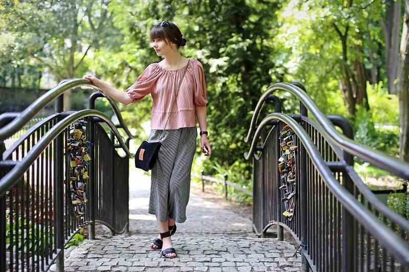 Spodnie typu culottes, płaskie sandały i plisy