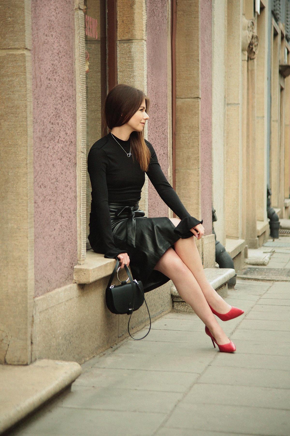 Kobieca stylizacja ze skórzaną spódnicą i czerwonymi szpilkami