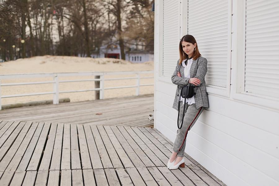 Spodnie z lampasem, marynarka oversize w kratę, białe pantofle, apaszka i torba z okrągłą, metalową rączką