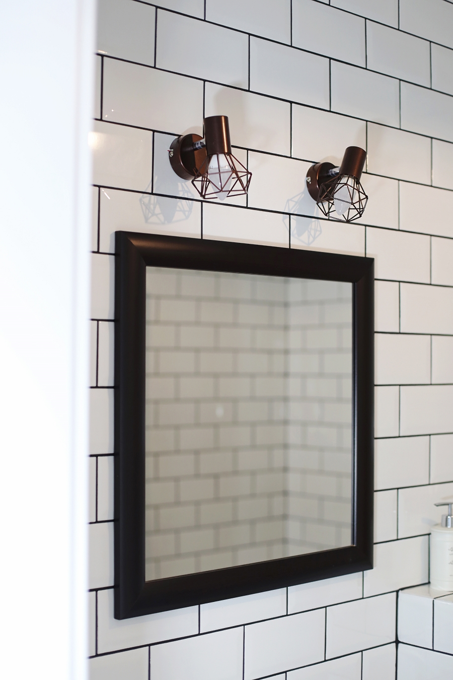 Mała łazienka – lustro z drewnianą ramą, lampy