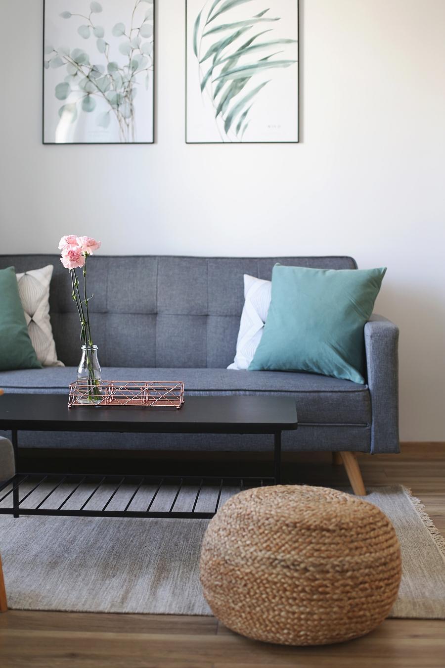 Salon z zielonymi akcentami – obrazy Margo Hupert, pufa pleciona, kanapa na drewnianych nóżkach, czarny stolik