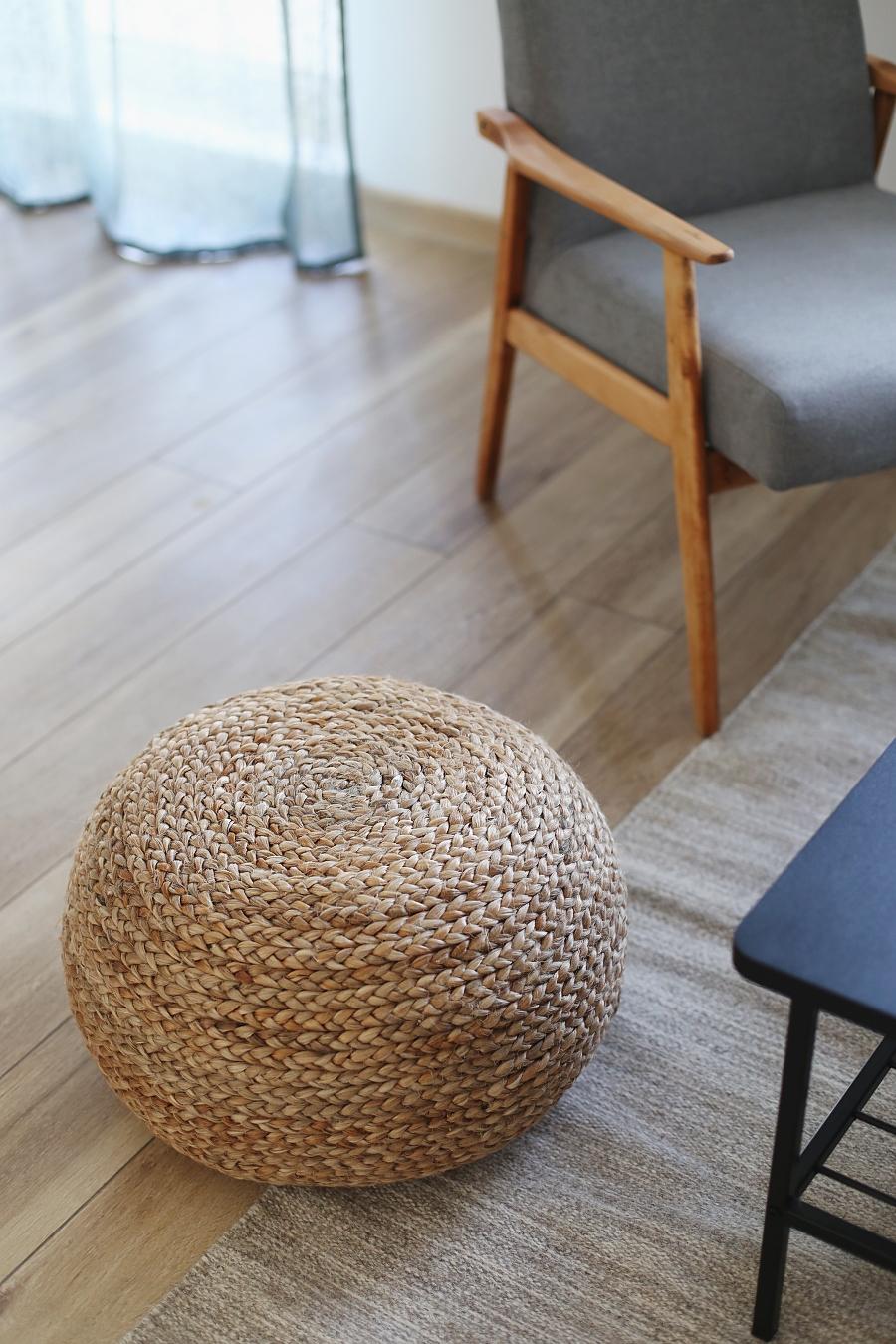 Salon z zielonymi akcentami - pleciona pufa z wikliny