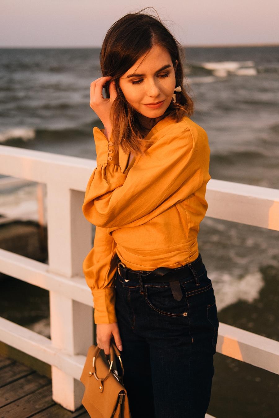 klasyczne jeansy i miodowa bluzka wiązana w pasie