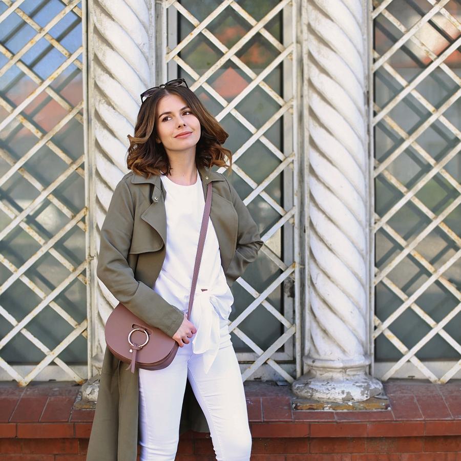 Biel od stóp do głów: białe jeansy, T-shirt z wiązaniem, torebka z okrągłą metalową obręczą, trencz