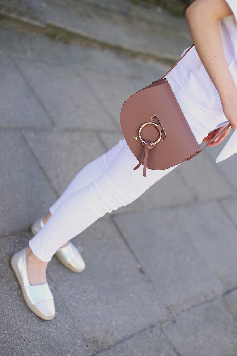 Białe jeansy, T-shirt z wiązaniem, torebka z okrągłą metalową obręczą