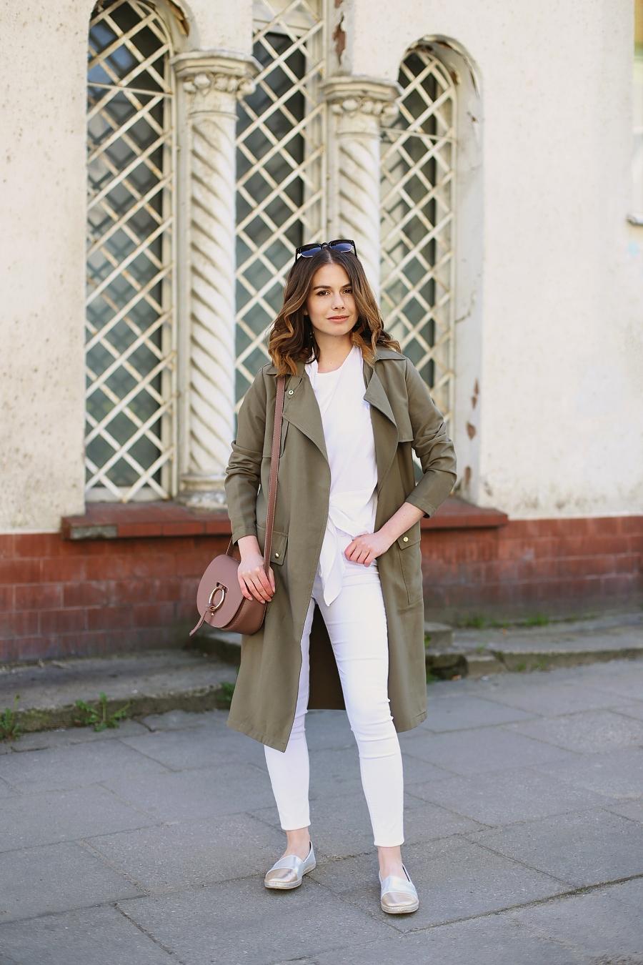 Białe jeansy, T-shirt z wiązaniem, torebka z okrągłą metalową obręczą, trencz