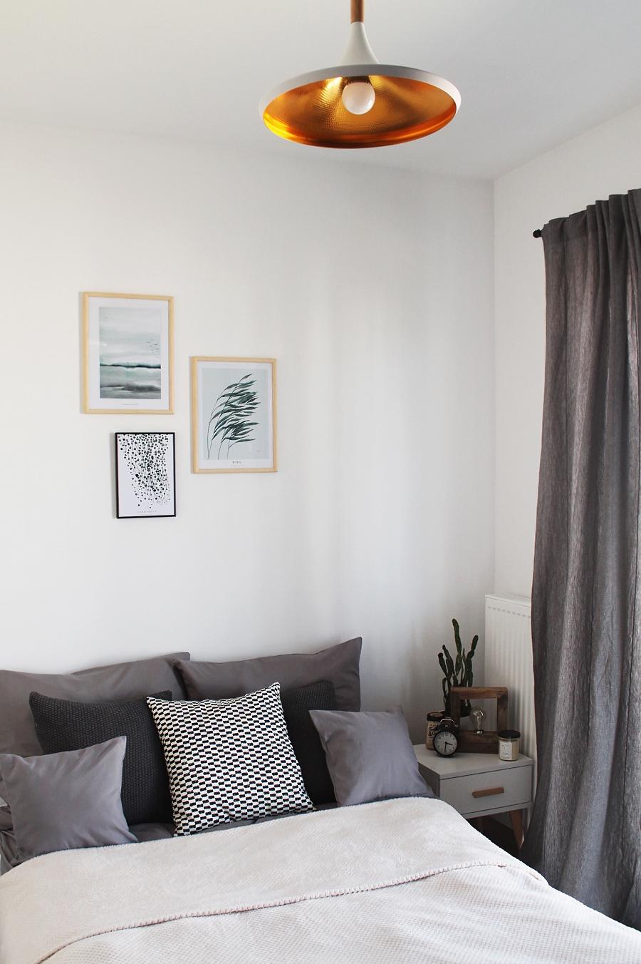 sypialnia - łóżko, szare zasłony, obrazy Margo Hupert