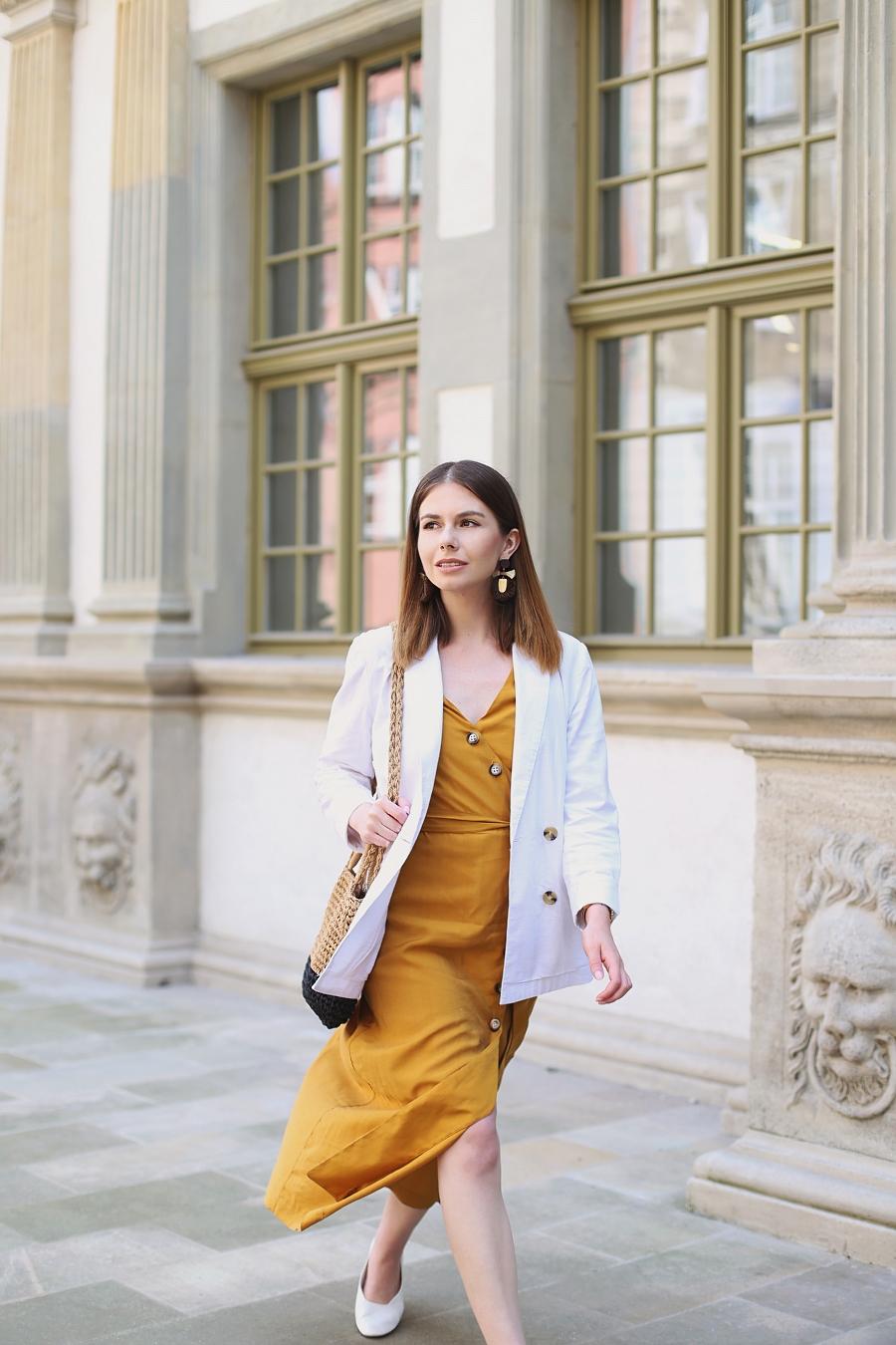 Miodowa sukienka 7/8, biała marynarka, pleciona torebka, białe pantofle, sznurkowe kolczyki