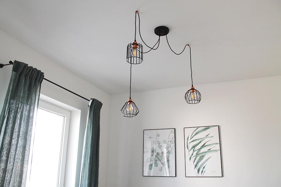 Salon z zielonymi akcentami – obrazy Margo Hupert, druciana lampa, lniane zasłony