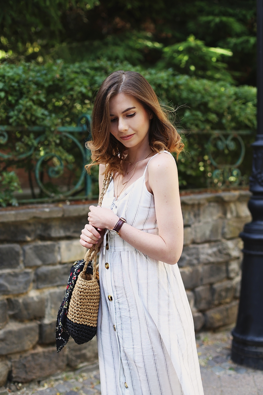 biała sukienka wiązana na biuście, naszyjnik kaskadowy, pleciona torebka