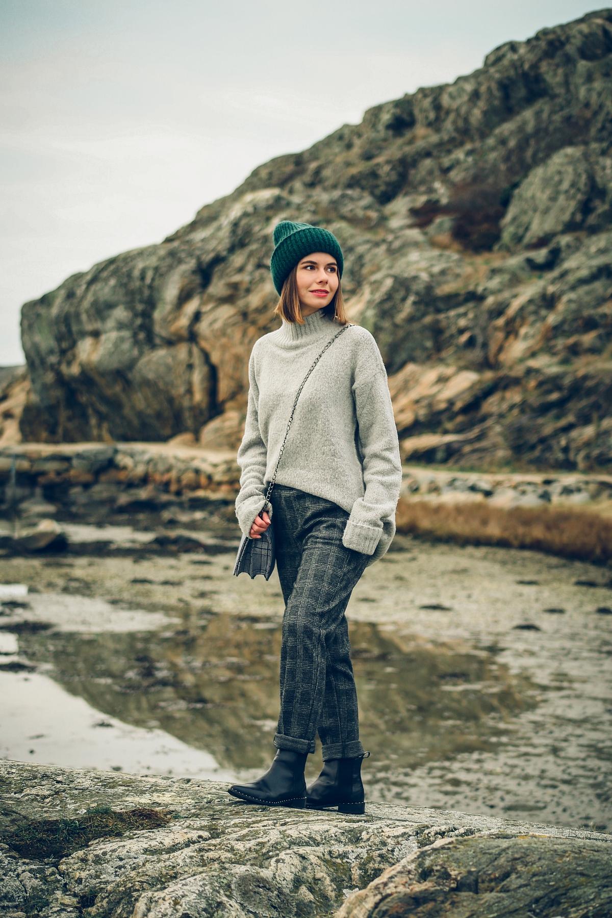 skandynawski look spodnie w kratę szary sweter zielona czapka